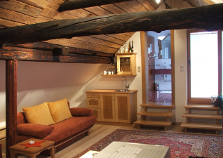 Nowadays the former barn in the upper floor is a spacious living room (Gallery view)